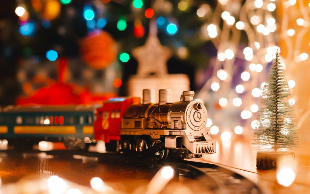 toy vintage steam locomotive on the floor under a decorated Christmas tree on a background of bokeh lights garland.